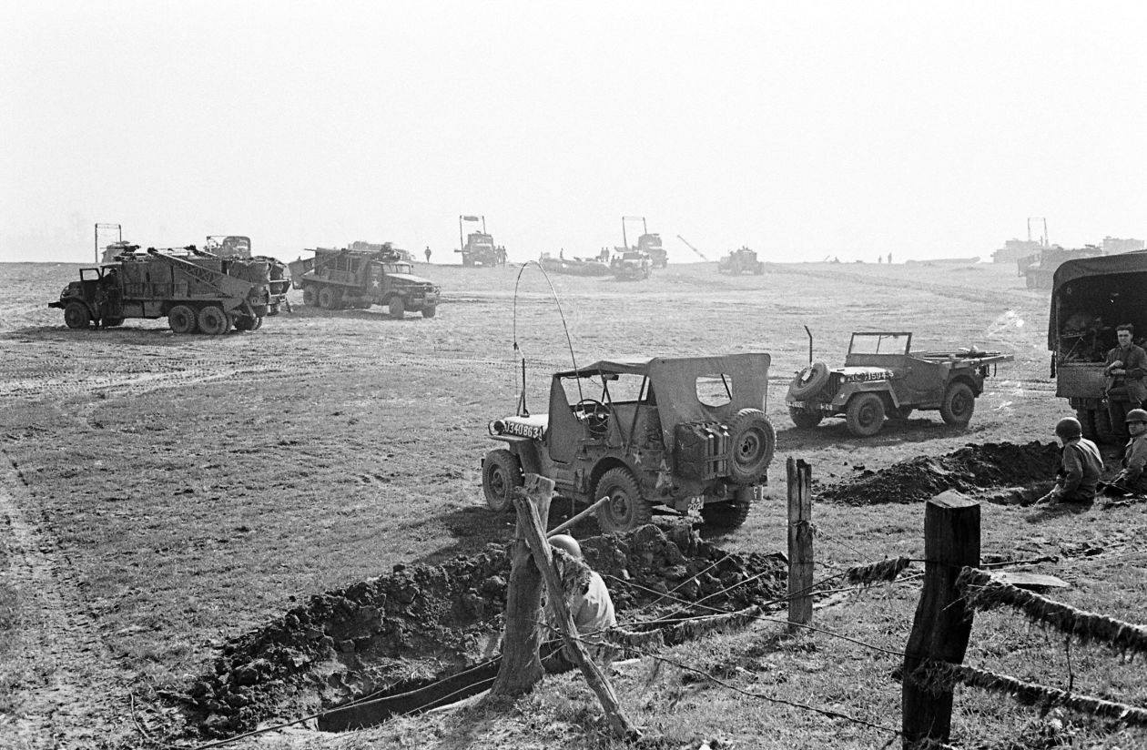 Jeeps of 202nd Engineer Combat Battalion foreground, Brockway B666 6x6 trucks of 17th AEB in the background.