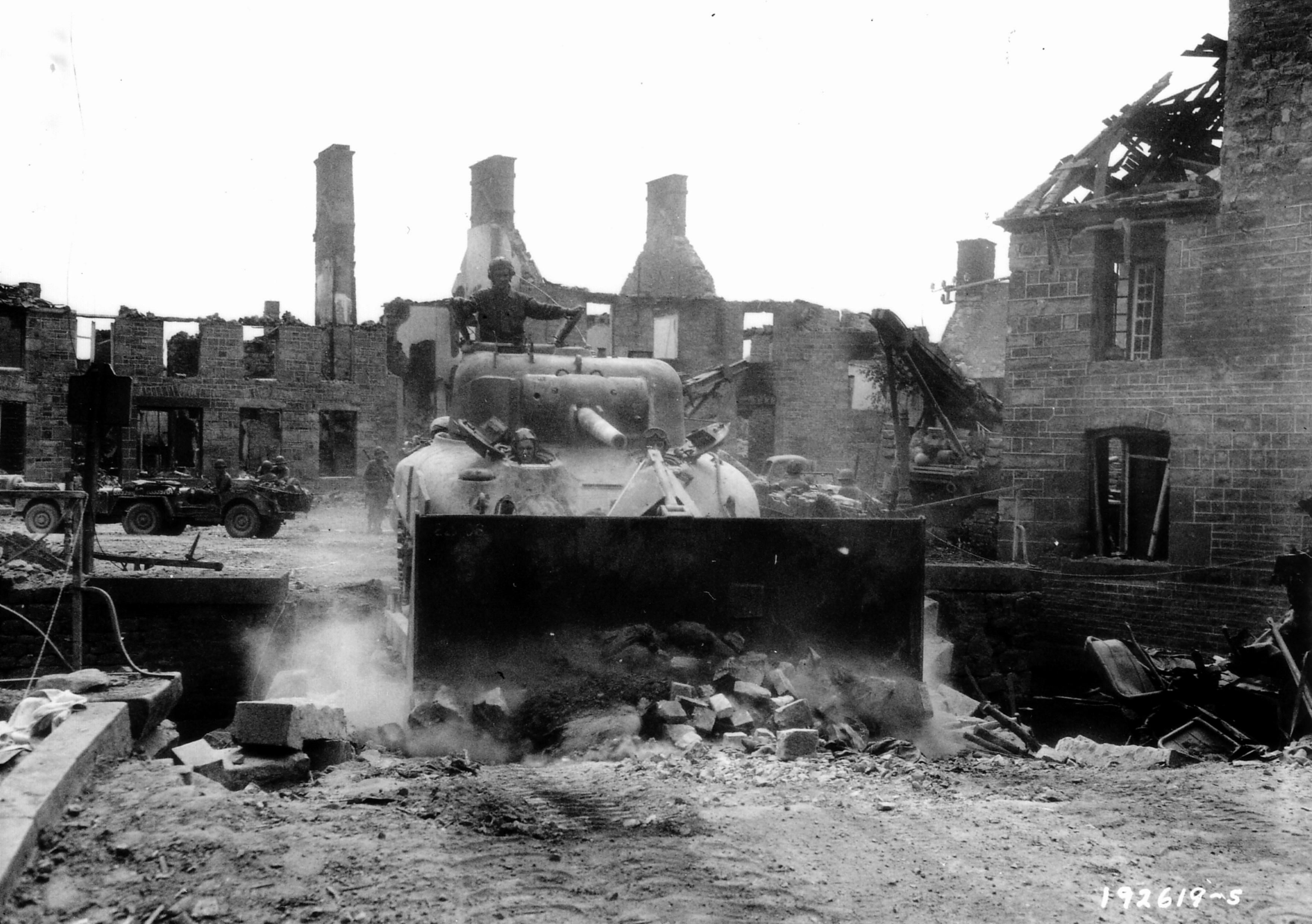 Tankdozer van de 17th Engineers, vlakschuiven van de opgeblazen brug bij de rivier Egrenne in de stad Saint-Sauveur-le Vicomte, the river Ögren (Egrenne)