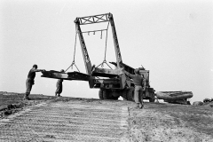 A Brockway bridge erector truck of 17thAEB, lowers treadway bridge sections down the bank of the Rhine.