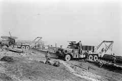 Unloading treadway bridge sections from Brockway B666 6x6 bridge erector trucks, possibly belonging to 17thAEB