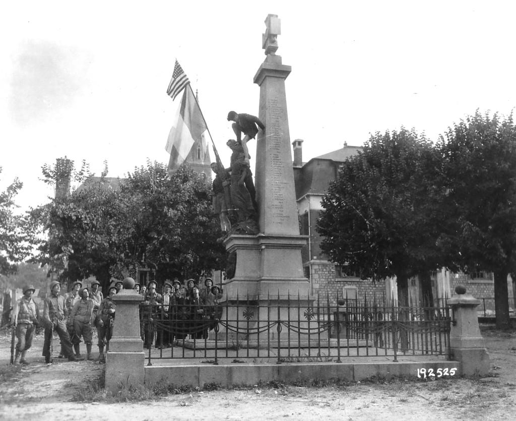 Trois jeunes gens escaladent le Monument aux morts sur la Place de Barenton sous le regard de soldats américains et de civils. Drapeau américain et drapeau français installés sur la statue.