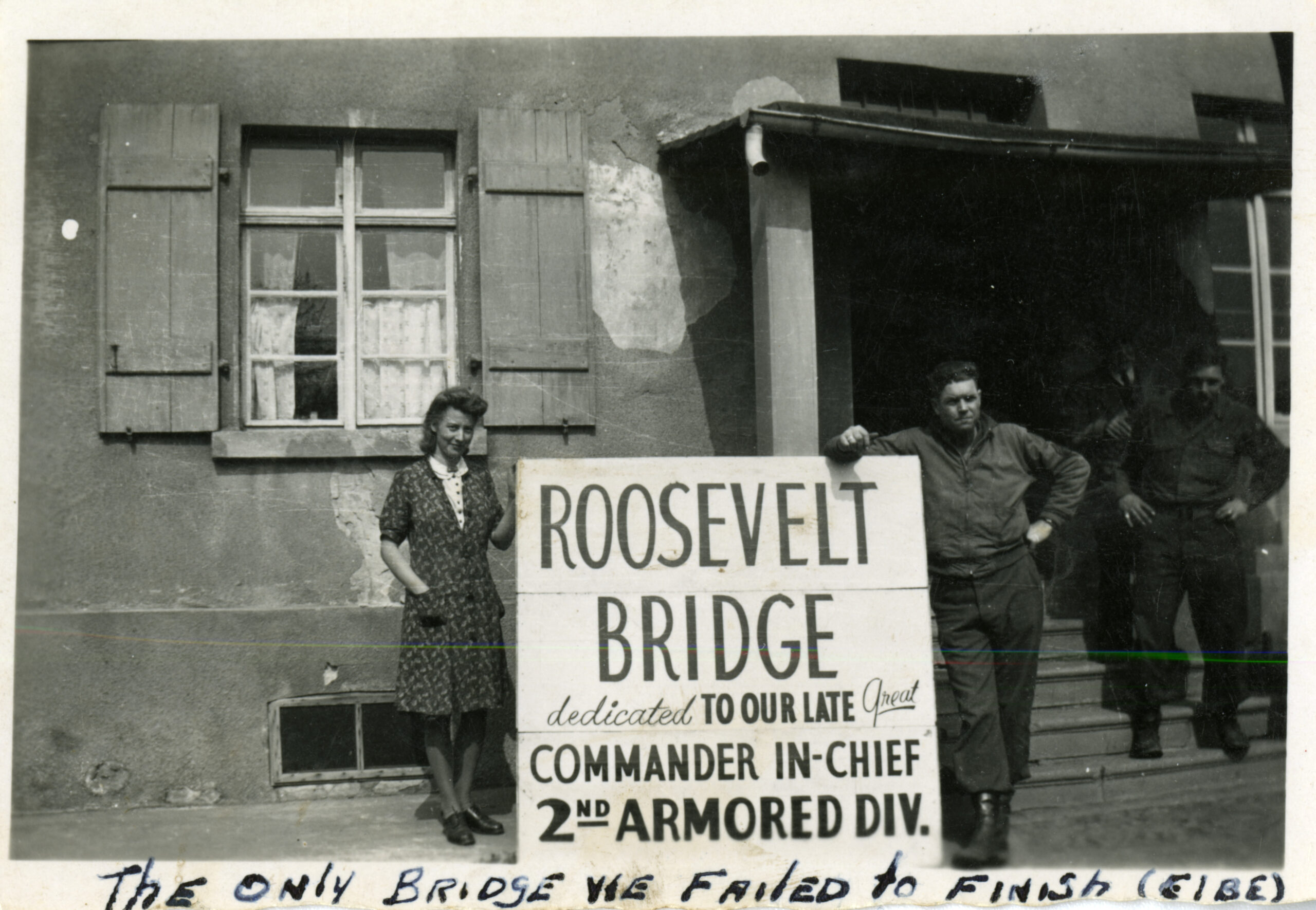 """American serviceman and a German woman posing with a sign that reads  """"Roosevelt Bridge dedicated to our late great Commander in-chief 2nd Armored Div."""" ; another serviceman is standing on the steps of the building in the background.  Personal caption on front: """"The only bridge we failed to finish (Elbe) ."""" Westerhusen, Germany. April 1945"""